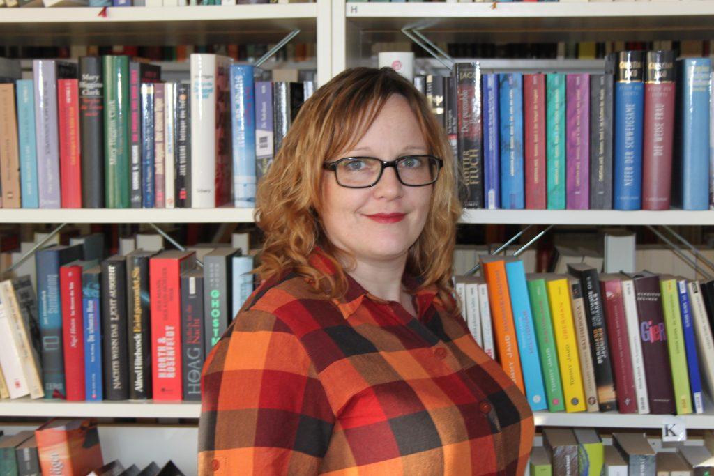 Profilbild einer Frau, Bücherregale im Hintergrund