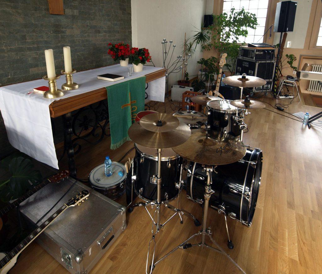 Schlagzeug, Gitarre und andere Musikinstrumente vor einem Altar.