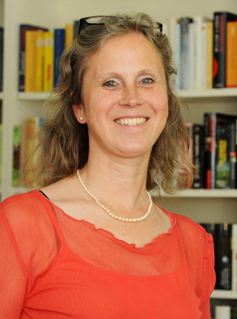 Profilbild einer Frau, im Hintergrund Bücherregale